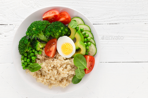 Healthy detox dish with egg, avocado, quinoa, spinach, fresh tomato, green peas and broccoli - Stock Photo - Images