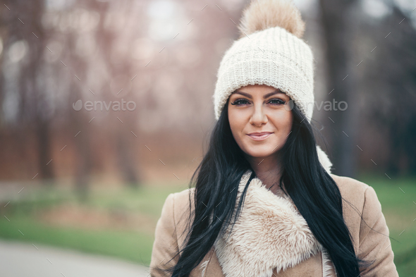 Portrait of a young woman wearing a coat and hat - Stock Photo - Images
