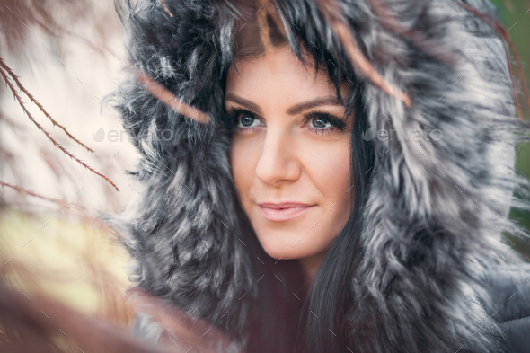 Beautiful woman wearing a fur hood winter coat - Stock Photo - Images
