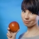 Attractive Brunette Girl Holding a Red Apple and Laughing on a Blue Wall - VideoHive Item for Sale