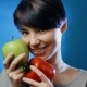 Attractive Brunette Girl Holding a Green Apple and Red Pepper Laughing on a Blue Wall - VideoHive Item for Sale