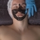 Spa. Applying a Black Mask To the Face of a Young Man - VideoHive Item for Sale