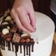 Woman Hands Decoration a Cake with Chocolate and Pretzels, Nuts - VideoHive Item for Sale