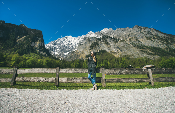 Female traveller posing in front of mountain view of Alps - Stock Photo - Images