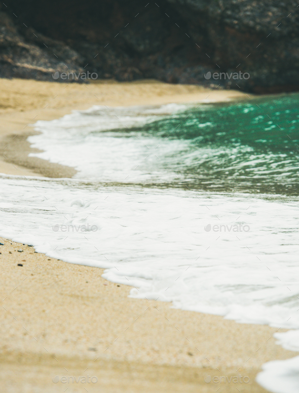 Blue sea water and sandy beach with rock at background, selective focus - Stock Photo - Images