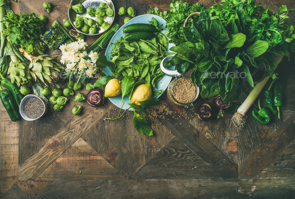 Spring healthy vegan food cooking ingredients over wooden background - Stock Photo - Images
