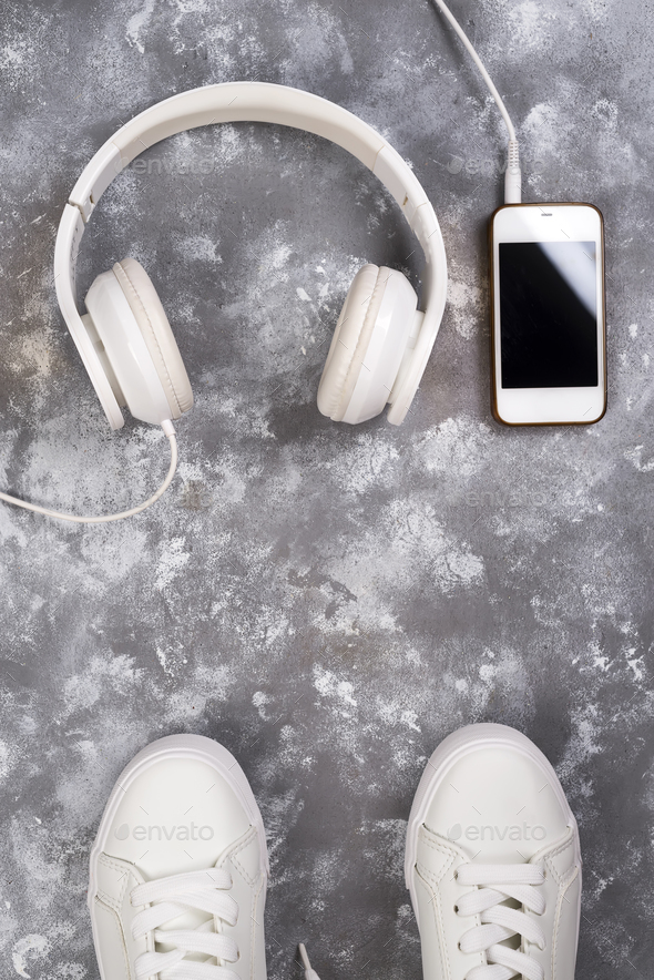 Flat lay Of White Sneakers On stone Background with phone and headphones. - Stock Photo - Images