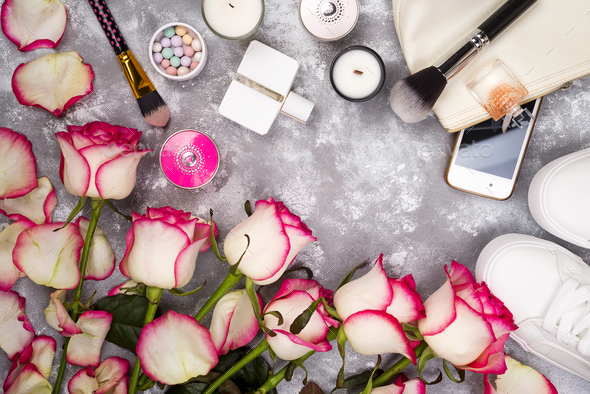 Bouquet of roses with cosmetics in perfume, phone and sneakers on a gray background with copy space - Stock Photo - Images