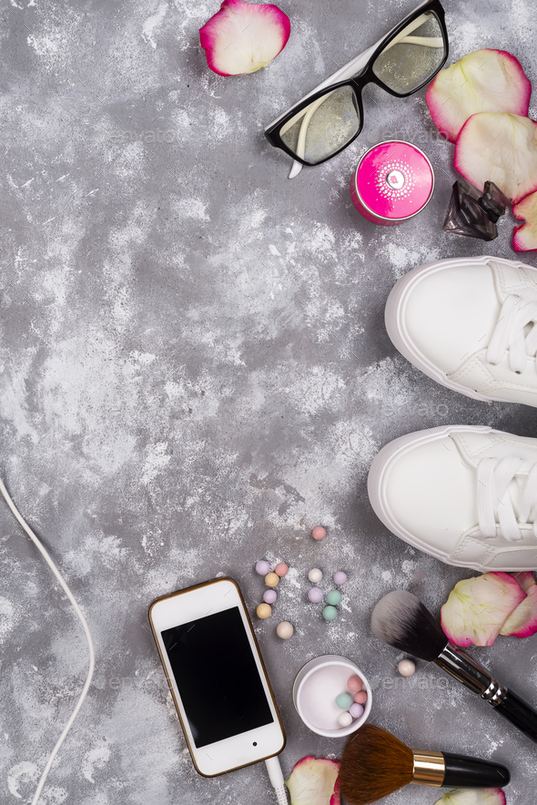 cosmetics with perfume, phone and sneakers on a gray background with copy space - Stock Photo - Images