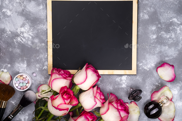 Roses and decorative cosmetics with a chalkboard - Stock Photo - Images