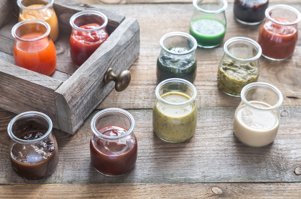 Assortment of sauces in the glass jars - Stock Photo - Images
