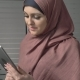 A Young Beautiful Girl in Pink Hijab Uses a Tablet, Speaks in a Video Chat, Greeting - VideoHive Item for Sale