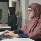 Young Beautiful Girl in Pink Hijab and Glasses Typing Working on Computer Look at the Camera Arab - VideoHive Item for Sale
