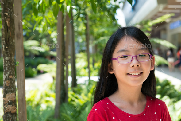 Cute Asian Chinese girl with glasses in park - Stock Photo - Images