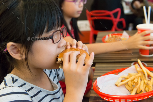 Asian kid eating a hamburger and french fries - Stock Photo - Images
