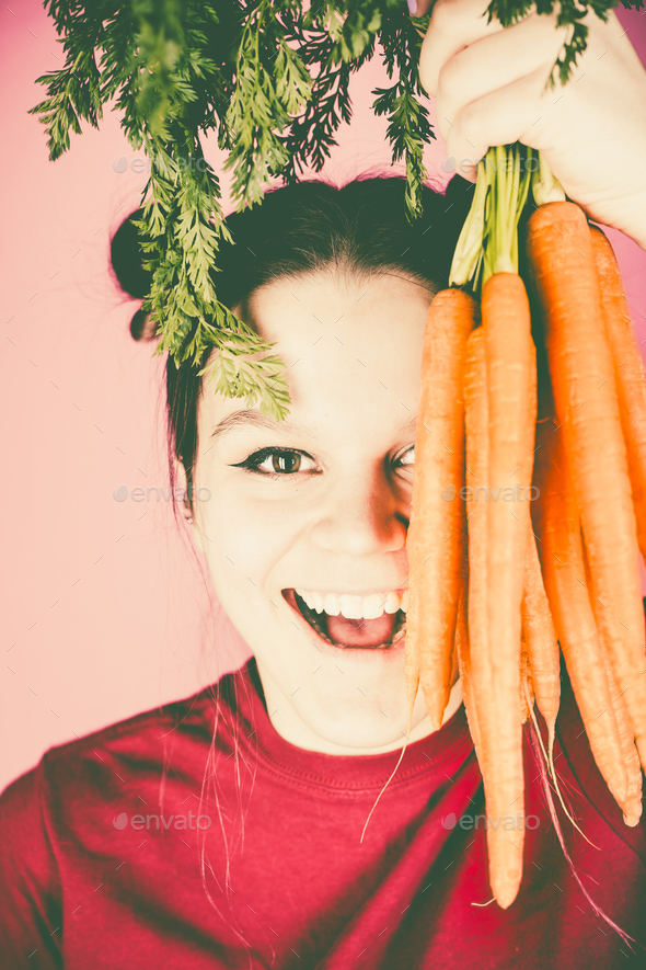 Teenage girl holding bunch of fresh carrots over pink background - Stock Photo - Images