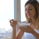 Woman Eating Cereal With Milk Out Of Bowl Standing At Window And Looking Outside - VideoHive Item for Sale