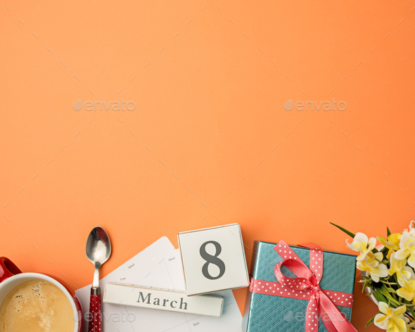 The top view of orange desk with cup of coffee, gift, flowers and notebook - Stock Photo - Images