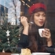 Look From the Outside at Charming Woman in Red Hat Drinking Coffee Sitting in the Cosy Cafe - VideoHive Item for Sale