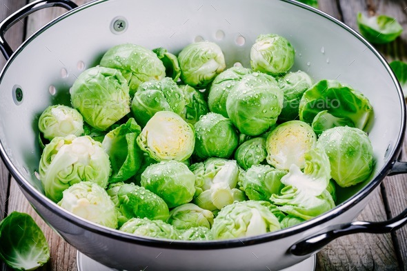 Fresh organic Brussels sprouts in a colander - Stock Photo - Images