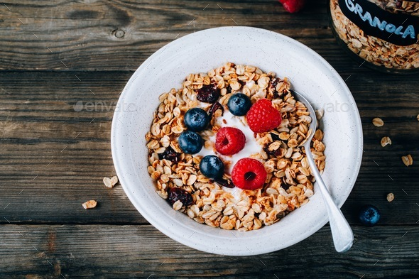 Healthy breakfast bowl. Homemade granola with natural yoghurt, blueberries and raspberries - Stock Photo - Images