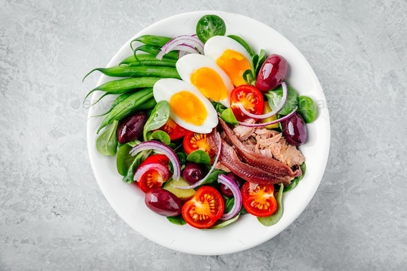 nicoise salad with tuna, anchovies, eggs, green beans, olives, tomatoes, red onions and salad leaves - Stock Photo - Images
