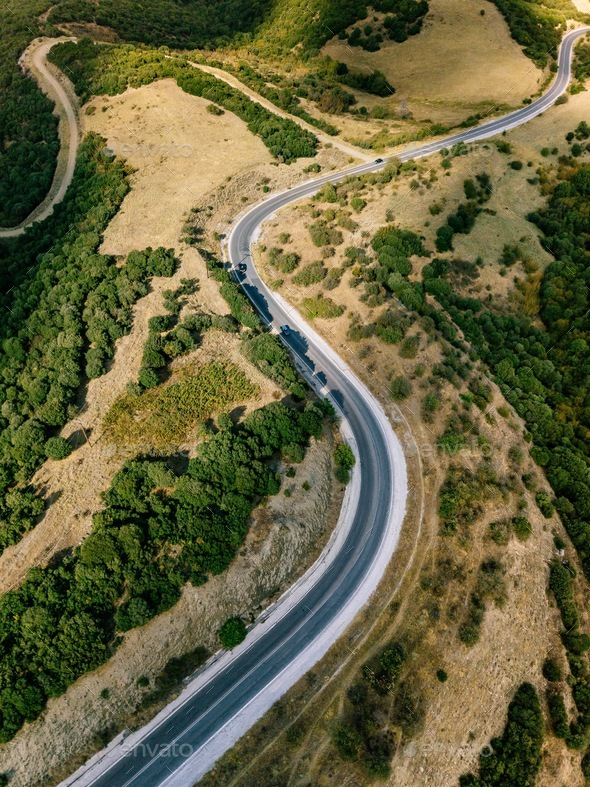 Aerial above view of a rural landscape with a curvy road running through it in Greece. - Stock Photo - Images