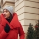 Beautiful Woman in Red Winter Jacket Walks Along the Street Covered with Snow in a Beautiful Old