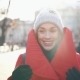 Girl in Grey Hat and Red Coat Walks Along the Street, Smiles and Looks Around in a Sunny Winter Day - VideoHive Item for Sale