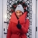 Happy Woman in Red Jackets Waits Before White Gates Outside