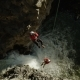 Crane Past Two Rock Climbers Climbing a Rope Over Waterfall While Canoyoneering - VideoHive Item for Sale