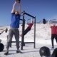 Group of Four Young Sportsmen Are Training on a Sport Area in Winter Day, One Is Pulling Up on Beam - VideoHive Item for Sale