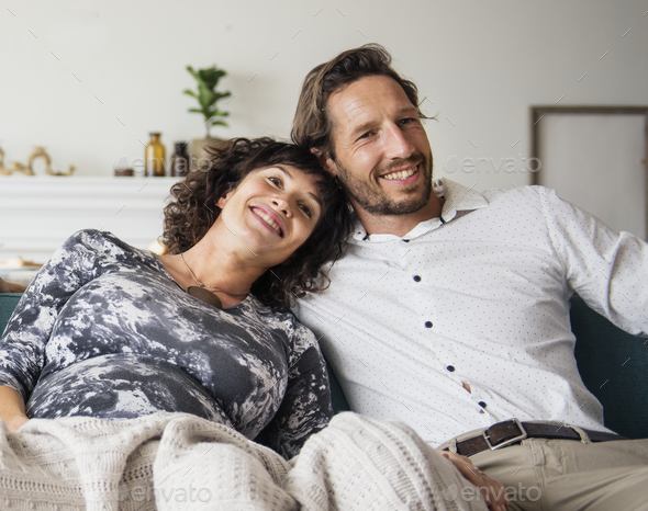 Couple relaxing in a living room - Stock Photo - Images