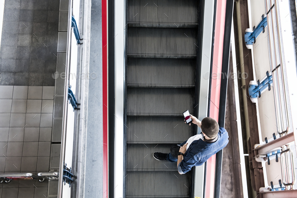 Man using a smartphone on the escalator - Stock Photo - Images
