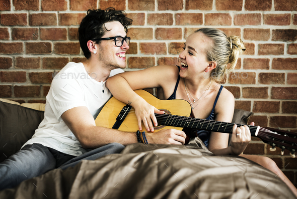 Caucasian couple playing guitar together - Stock Photo - Images
