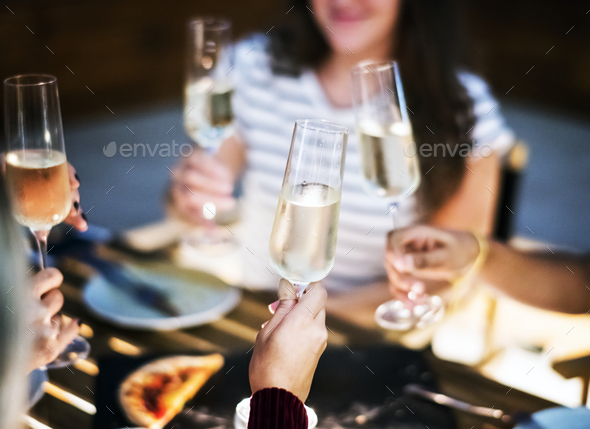 Girl friends toasting at dinner together at a rooftop bar - Stock Photo - Images
