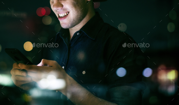 Happy young adult male using a smartphone in a night cityscape - Stock Photo - Images
