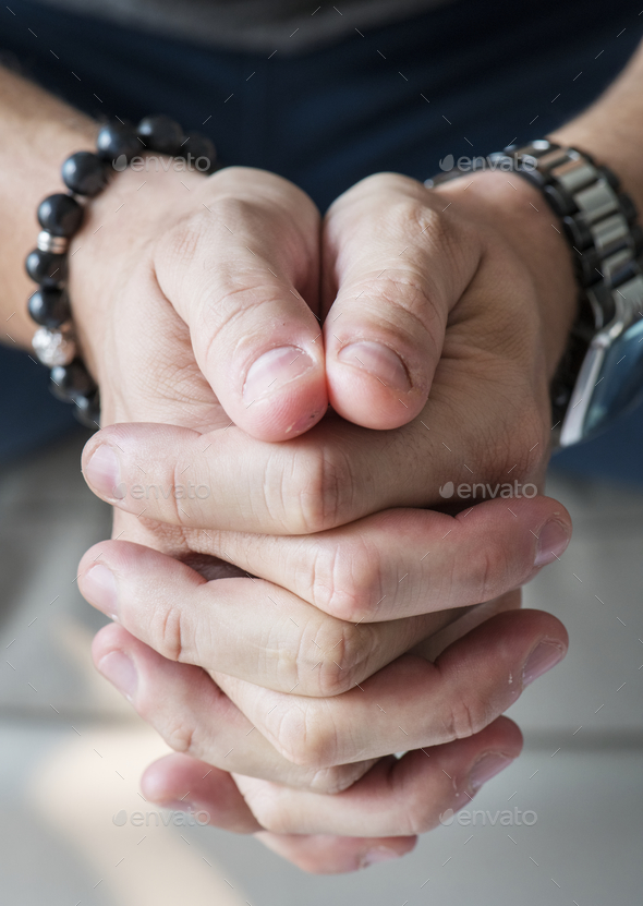 Closeup of white hands in praying gesture - Stock Photo - Images