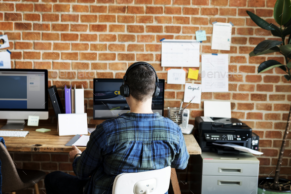 Rear view of Caucasian man using computer - Stock Photo - Images