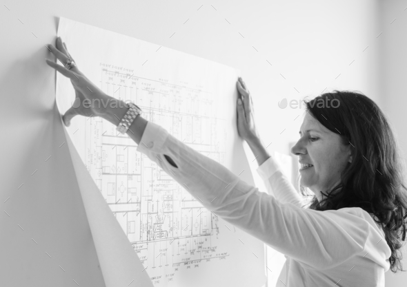 White architect showing building plan on white wall - Stock Photo - Images