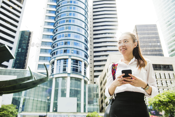 Asian businesswoman in a city - Stock Photo - Images