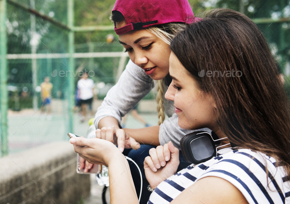 Young adult female friends listening to music through their smar - Stock Photo - Images