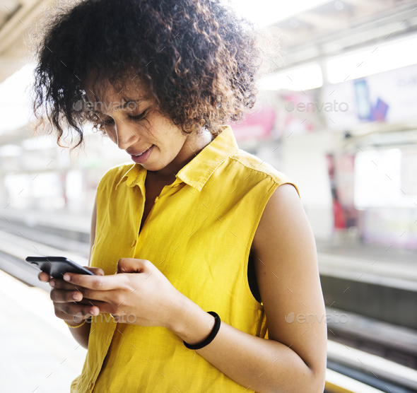Young woman using a smartphone on the subway station - Stock Photo - Images