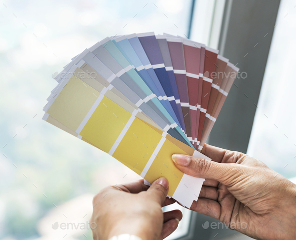 Closeup of hands holding color swatch - Stock Photo - Images