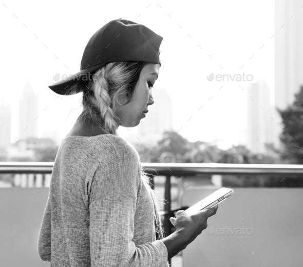 Young woman using a smartphone in the cityscape - Stock Photo - Images