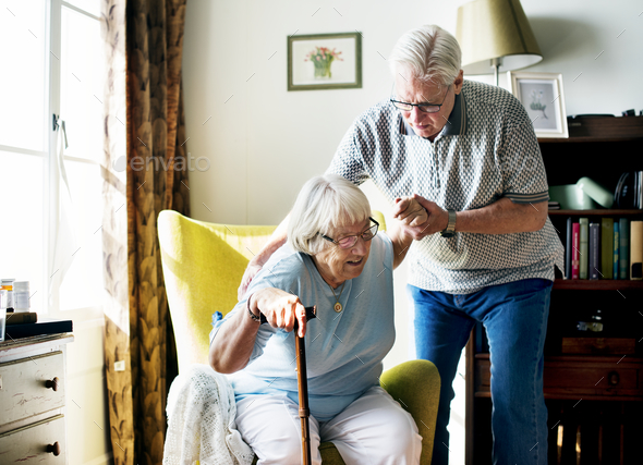 Senior man helping senior woman to stand - Stock Photo - Images
