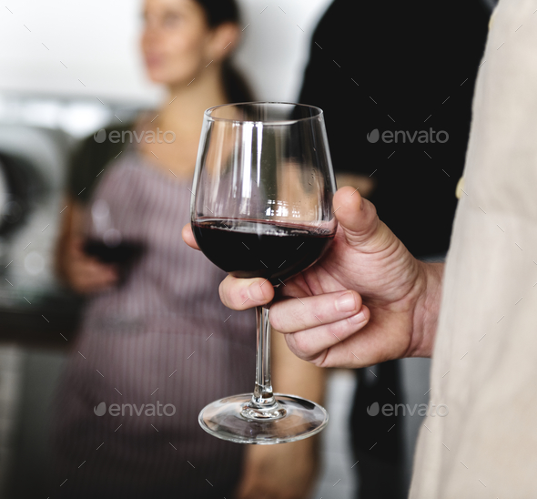 Closeup of man holding red wine glass - Stock Photo - Images