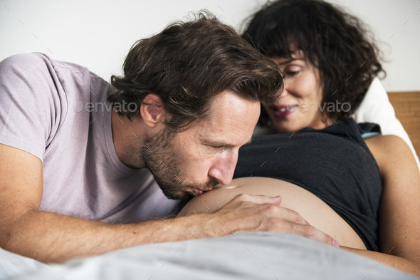 Husband kissing a baby bump - Stock Photo - Images