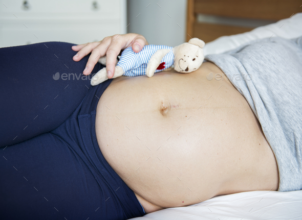 Pregnant woman sleeping on bed - Stock Photo - Images