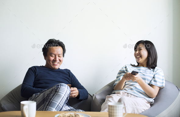 Asian couple watching movie at home together - Stock Photo - Images